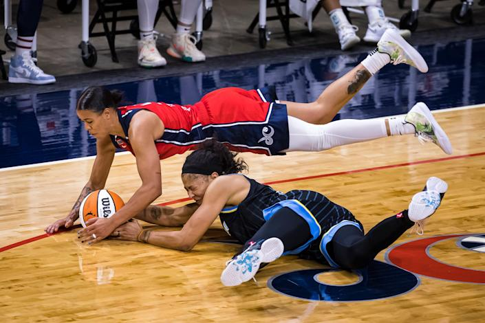 One basketball player is seen diving over another as she holds the ball.