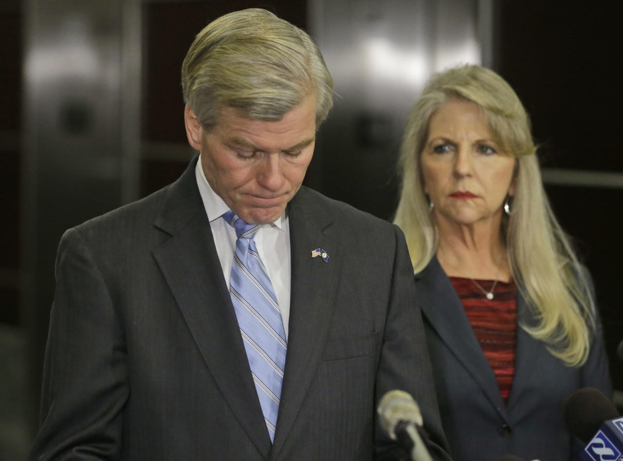 Former Virginia Governor Bob McDonnell takes a moment while making a statement as his wife, Maureen, right, looks on during a news conference in Richmond, Va., Tuesday, Jan. 21, 2014. McDonnell and his wife were indicted Tuesday on corruption charges after a monthslong federal investigation into gifts the Republican received from a political donor. (AP Photo/Steve Helber)