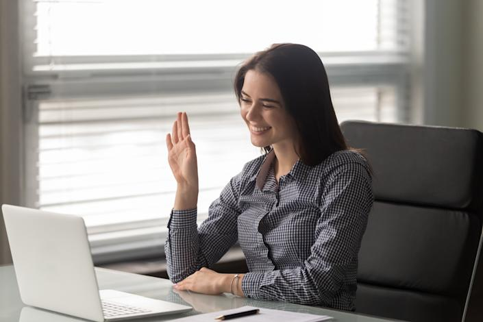 Woman sit at desk looks at pc screen makes video call using webcam, on-line teacher wave hand greets learner in distance lesson, modern application user, job interview, distant communication concept