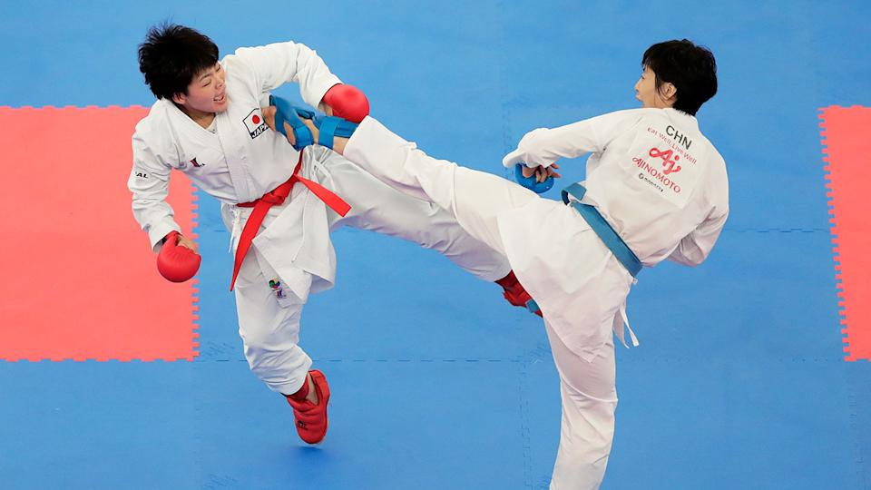 Two karate competitors kicking each other in a Kumite contest.