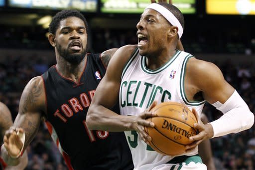 Boston Celtics forward Paul Pierce (34) drives past Toronto Raptors forward Amir Johnson (15) in the second quarter of an NBA basketball game in Boston, Wednesday, Jan. 18, 2012. (AP Photo/Elise Amendola)