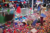 Revellers take photos while lying in confetti after New Year celebrations in Times Square, Midtown, New York January 1, 2014. REUTERS/Adrees Latif