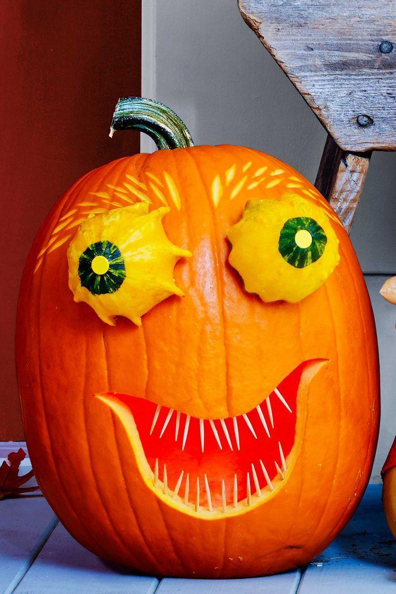 "<p>Hollow out medium tall pumpkin from the bottom. Carve mouth shape, then stick toothpicks into top and bottom to create teeth. For eyes, slice off bottom of 2 small gourds; attach with toothpicks. Push in <span class=""redactor-unlink"">yellow thumbtacks</span> for pupils. Use highlighter to draw dashes for eyebrows. Remove gourd eyes, etch in eyebrows using linoleum cutter, then replace eyes.</p>"