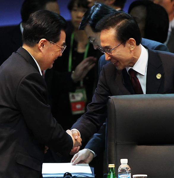 South Korean President Lee Myng-bak, right, shakes hands with Chinese President Hu Jintao during the Nuclear Security Summit in the Coex Center in Seoul, South Korea Tuesday March 27, 2012. (AP Photo/Yonhap) KOREA OUT
