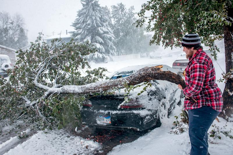 Zack Ruml, 20, of Rapid City, S.D, lifts a heavy crab apple tree branch off of his 1998 Pontiac Gran Prix on Friday, Oct. 4, 2013. The branch smashed the rear window and dented the trunk of the car. Trees in the city are still fully leaved and the heavy snow is breaking trees throughout the city. Blizzards rolled into parts of Wyoming and South Dakota on Friday, bringing the snow-savvy states to an unseasonably early winter standstill. (AP Photo/Steve McEnroe)