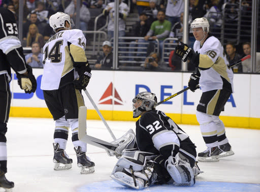 Pittsburgh Penguins left wing Chris Kunitz, left, celebrates his goal with left wing Jussi Jokinen, of Finland, as Los Angeles Kings goalie Jonathan Quick sits on the ice during the first period of an NHL hockey game, Thursday, Jan. 30, 2014, in Los Angeles. (AP Photo)