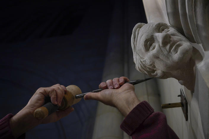 Stone carver Sean Callahan uses a chisel and mallet as he works on a limestone head of Holocaust survivor and Nobel Peace Prize winning author Elie Wiesel in the Human Rights Porch at the Washington National Cathedral, Thursday, April 1, 2021. (AP Photo/Carolyn Kaster)