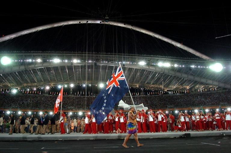 Weightlifter Sam Pera parades the Cook Islands flag during the opening ceremony of the 2004 Olympic Games. The tiny Pacific Ocean nation is considering a name change to something more traditional