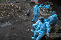 Health workers wearing personal protective equipment wait near the body of a person who died of COVID 19 at a cremation ground in Gauhati, India, Thursday, Sept. 10, 2020. India is now second in the world with the number of reported coronavirus infections with over 5.1 million cases, behind only the United States. Its death toll of only 83,000 in a country of 1.3 billion people, however, is raising questions about the way it counts fatalities from COVID-19. (AP Photo/Anupam Nath)