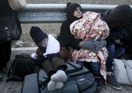 Syrian refugees rest next to a highway as a group of more than 100 Syrian refugees who crossed the Greek-Turkish land borders the previous night is stopped by Greek police near the village of Thourio at the regional unit of Evros in northeastern Greece, January 24, 2016. REUTERS/Alexandros Avramidis