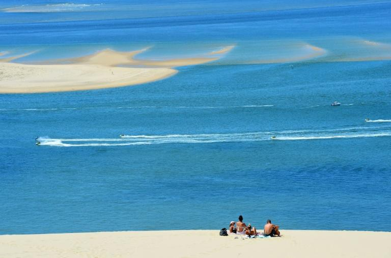 """People enjoy a sunny day atop Europe's tallest sand dune, the """"Dune du Pilat"""", after its reopening in La Teste-de-Buch, France (AFP Photo/MEHDI FEDOUACH)"""
