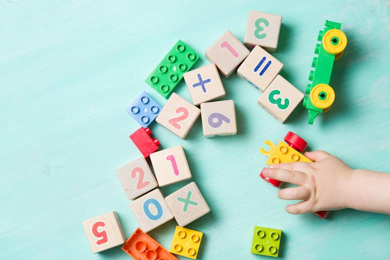 Child playing with wooden cubes with numbers and colorful toy bricks on a turquoise wooden background. Toddler learning numbers. Hand of a child taking toys.
