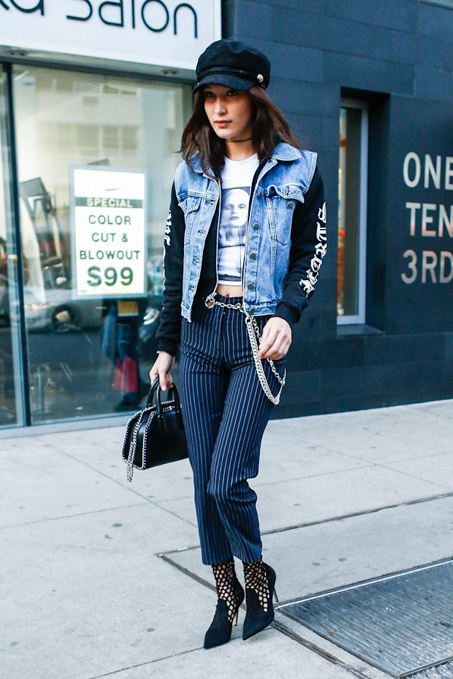 "<p>Gigi's younger sister Bella was also spotted in the brand in early January. She paired the label's <a rel=""nofollow"" href=""https://miaouxx.com/collections/denim/products/brigitte-jean-pinstripe"">$325 pinstripe pants</a> with a graphic tee, a hoodie, and a denim vest. She also added the Miaou's $85 <a rel=""nofollow"" href=""https://miaouxx.com/collections/belts/products/chain-belt"">metal chain-link belt </a>and $325 <a rel=""nofollow"" href=""https://miaouxx.com/collections/belts/products/side-piece"">side piece</a> to the look. (Photo: AKM-GSI) <br /><br /></p>"