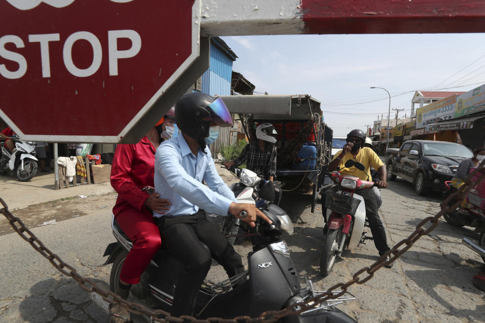 Residents are stopped near Phnom Penh International airport in Phnom Penh, Cambodia, Thursday, April 15, 2021. Cambodia's leader on Wednesday said that the country's capital Phnom Penh will be locked down for two weeks following a sharp rise in COVID-19 cases. (AP Photo/Heng Sinith)