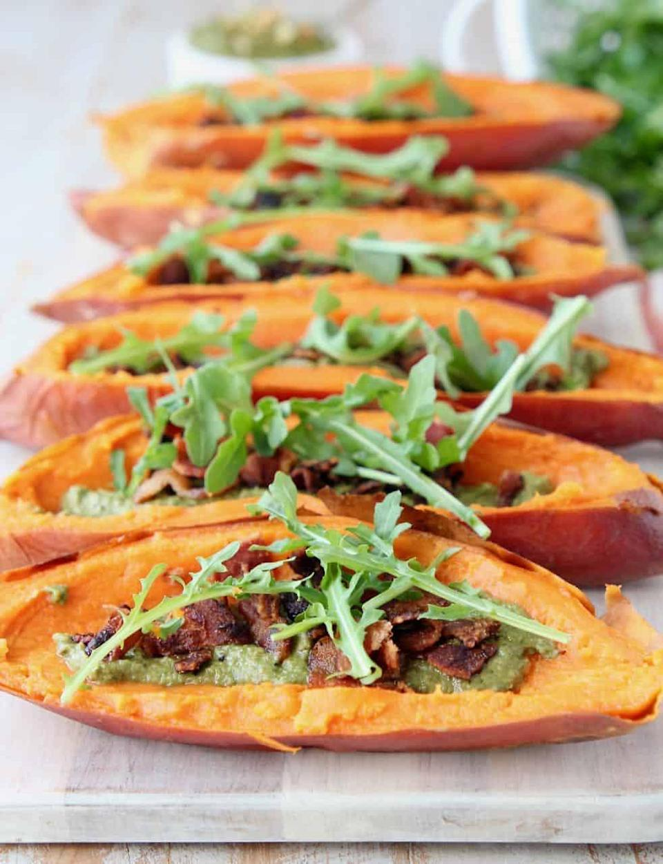 "<p>Usually sweet potatoes are covered with marshmallows on Thanksgiving, but these sweet potato skins are a healthy alternative to the sugary sweet dish. The skins are filled with sage pesto, bacon, and arugula for a tasty side dish. The original recipe makes eight potato skins, so cut the recipe in half or fourths depending on how many potato skins you want to eat. </p> <p><strong>Get the recipe:</strong> <a href=""http://whitneybond.com/paleo-sweet-potato-skins-with-sage-pesto-and-bacon/#wprm-recipe-container-32238"" class=""link rapid-noclick-resp"" rel=""nofollow noopener"" target=""_blank"" data-ylk=""slk:sweet potato skins with sage pesto and bacon"">sweet potato skins with sage pesto and bacon</a></p>"