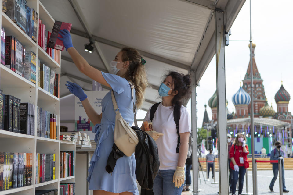 A woman takes a book from a shelf at an outdoor book market set up, in Red Square, Moscow, Russia, Saturday, June 6, 2020. Muscovites clad in face masks and gloves ventured into Red Square for an outdoor book market, a small sign of the Russian capital's gradual efforts to open up amid coronavirus concerns. (AP Photo/Alexander Zemlianichenko Jr)