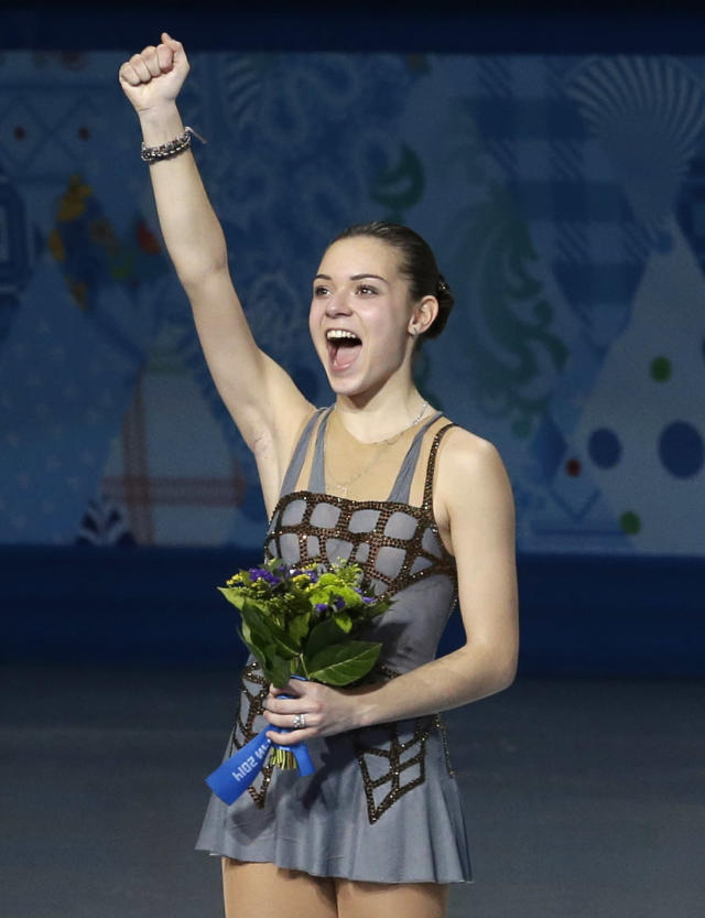 Adelina Sotnikova of Russia celebrates on the podium as she celebrates placing first during the flower ceremony for the women's free skate figure skating final at the Iceberg Skating Palace during the 2014 Winter Olympics, Thursday, Feb. 20, 2014, in Sochi, Russia. (AP Photo/Darron Cummings)