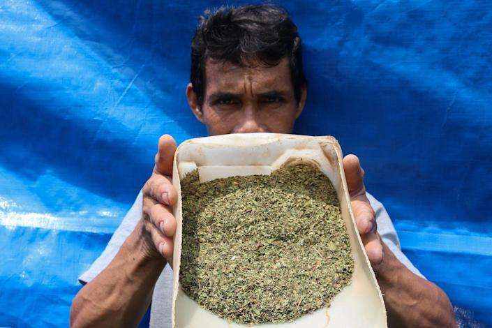 A man holds a container of ground kratom.
