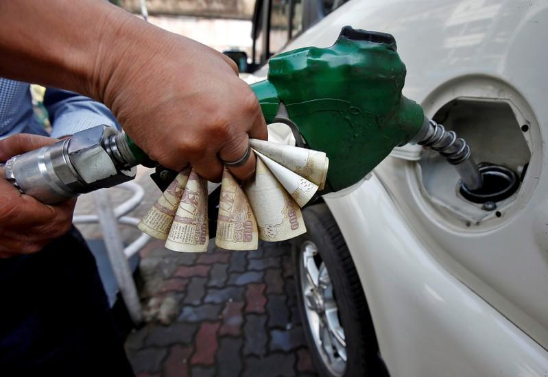 FILE PHOTO: A worker fills diesel in a car as he holds 500 Indian rupee banknotes at a fuel station in Kolkata