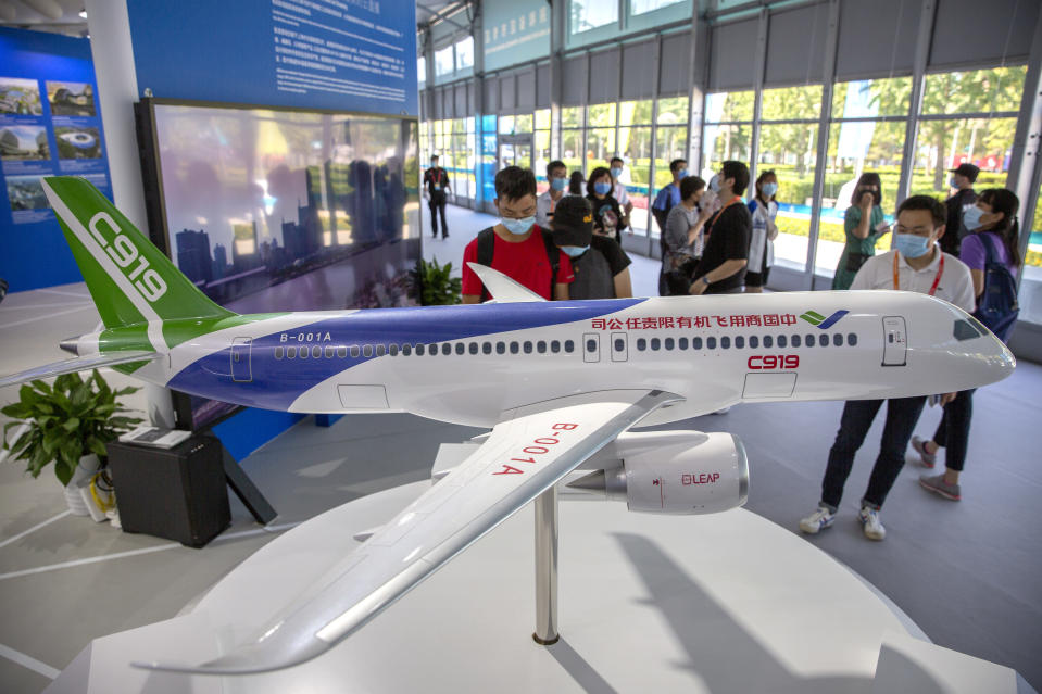 People look at a model of China's domestically-made C919 passenger jet at the China International Fair for Trade in Services (CIFTIS) in Beijing, Saturday, Sept. 5, 2020. Chinese leaders are shifting focus from the coronavirus back to long-term goals of making China a technology leader at this year's highest-profile political event, the meeting of its ceremonial legislature, amid tension with Washington and Europe over trade, Hong Kong and human rights. (AP Photo/Mark Schiefelbein)