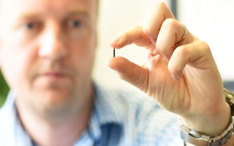 Steven Northam with one of the microchips. - Credit: Morten Watkins/Solent News & Photo Agency