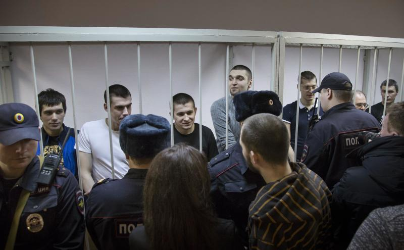 Defendants stand behind bars in a cage at a court room in Moscow, Russia, Monday, Feb. 24, 2014, where hearings started against opposition activists detained on May 6, 2012 during a rally at Bolotnaya Square. A Moscow judge on Friday, Feb. 21, 2014, convicted eight anti-government protesters of rioting during a 2012 protest against Vladimir Putin, following a trial seen as part of the Kremlin's efforts to stifle dissent. (AP Photo/Alexander Zemlianichenko)