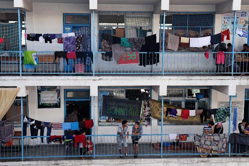 Palestinians displaced by Israeli bombardments on the Gaza Strip talk in the corridor of a United Nations school that has been turned into a temporary shelter, on August 8, 2014, in Gaza City