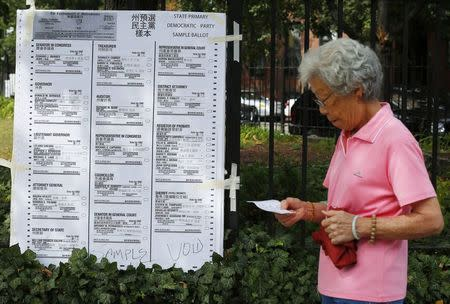 A woman arriving at a polling station walks past an enlarged copy of the democratic primary ballot in primary election day in Boston, Massachusetts September 9, 2014. REUTERS/Brian Snyder