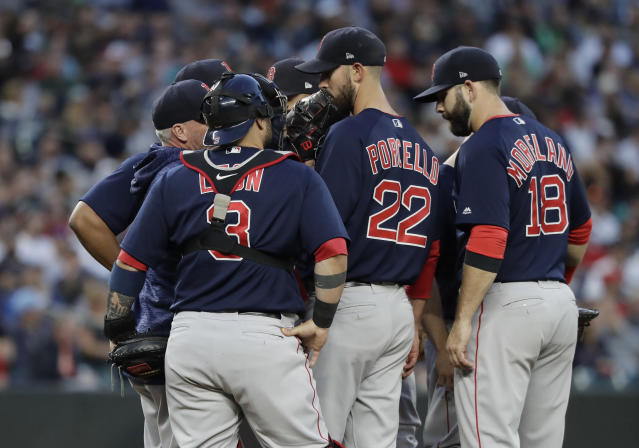 Boston Red Sox starting pitcher Rick Porcello (22) talks with teammates on the mound during the fifth inning of the team's baseball game against the Seattle Mariners, Friday, June 15, 2018, in Seattle. Porcello finished the inning, getting out of a bases-loaded jam and giving up one run. (AP Photo/Ted S. Warren)