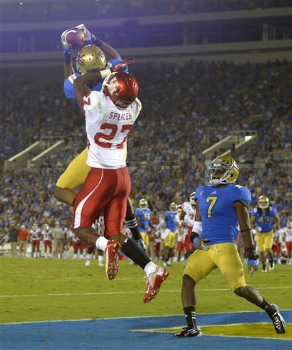 UCLA cornerback Sheldon Price, upper left, intercepts a pass intended for Houston wide receiver Daniel Spencer, center, as UCLA safety Tevin McDonald looks on during the second half of their NCAA college football game, Saturday, Sept. 15, 2012, in Pasadena, Calif. (AP Photo/Mark J. Terrill)
