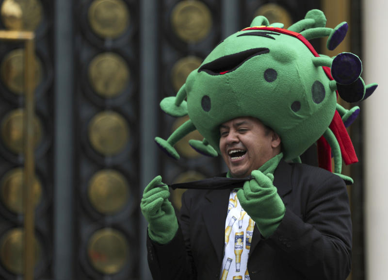 A street artist costumed as the new coronavirus laughs during a protest demanding the resumption of economic activities after not being able to earn a living since March because of the restrictions to curb the spread of COVID-19 in Mexico City, Thursday, June 11, 2020. Mexico's industrial activity plunged by nearly 30% in April compared to a year earlier as the economy ground to a halt under measures aimed at slowing the spread of the virus. (AP Photo/Fernando Llano)