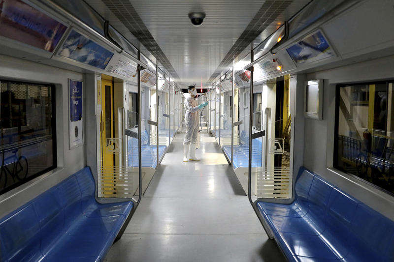A worker disinfects subway trains against coronavirus in Tehran, Iran, in the early morning of Wednesday, Feb. 26, 2020. Iran's government said Tuesday that more than a dozen people had died nationwide from the new coronavirus, rejecting claims of a much higher death toll of 50 by a lawmaker from the city of Qom that has been at the epicenter of the virus in the country. (AP Photo/Ebrahim Noroozi)