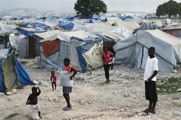 Haitians made homeless in the 2010 earthquake stand outside their tents on the outskirts of Port-au-Prince, January 13, 2011.