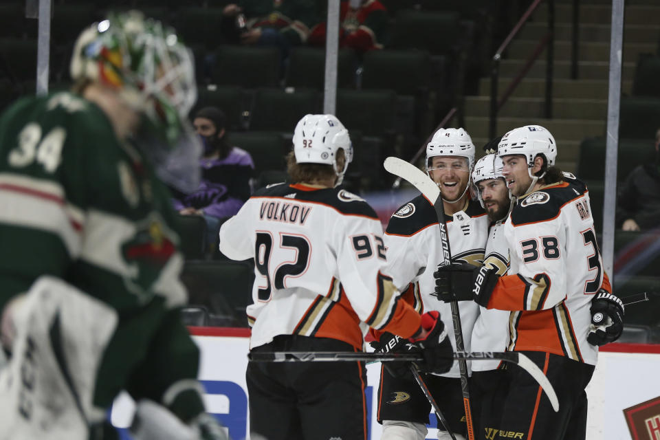 Anaheim Ducks' Adam Henrique (14) is surrounded by teammates after scoring a goal against the Minnesota Wild during the second period of an NHL hockey game Friday, May 7, 2021, in St. Paul, Minn. (AP Photo/Stacy Bengs)