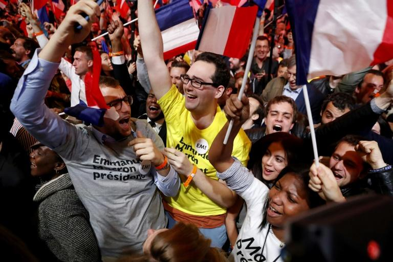 Supporters of Emmanuel Macron cheer following the announcement that he is on course to qualify for the run-off in France's presidential election in Paris on April 23, 2017