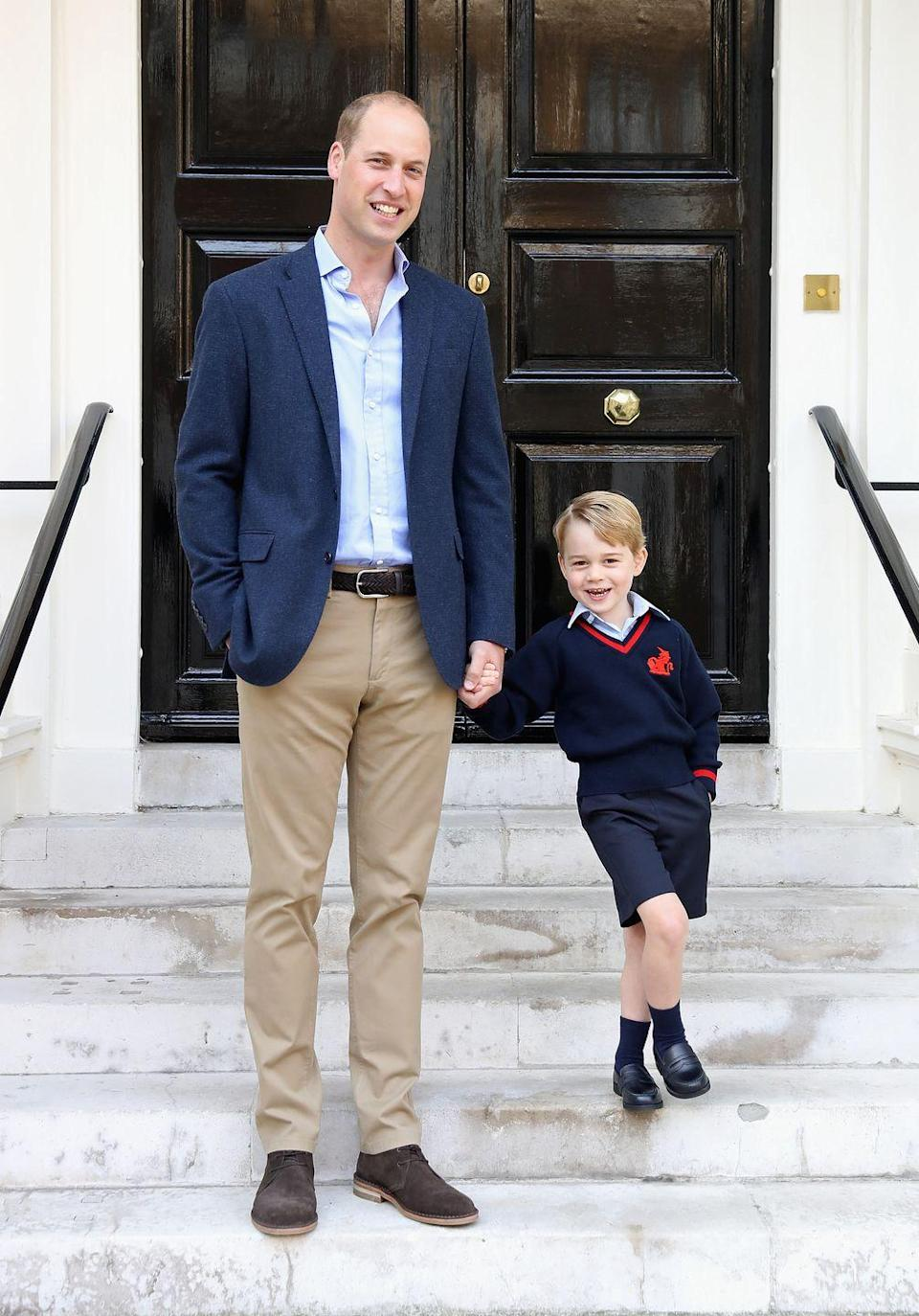 <p>Prince George proudly holds hands with Prince William outside Kensington Palace on George's first day of school at Thomas's Battersea in September 2017. </p>