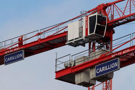 A worker walks along a crane on Carillion's Midland Metropolitan Hospital construction site in Smethwick