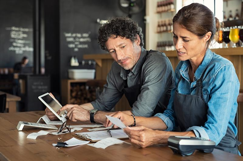 Man and woman looking through receipts with a tablet and calculator on the table where they're spread out