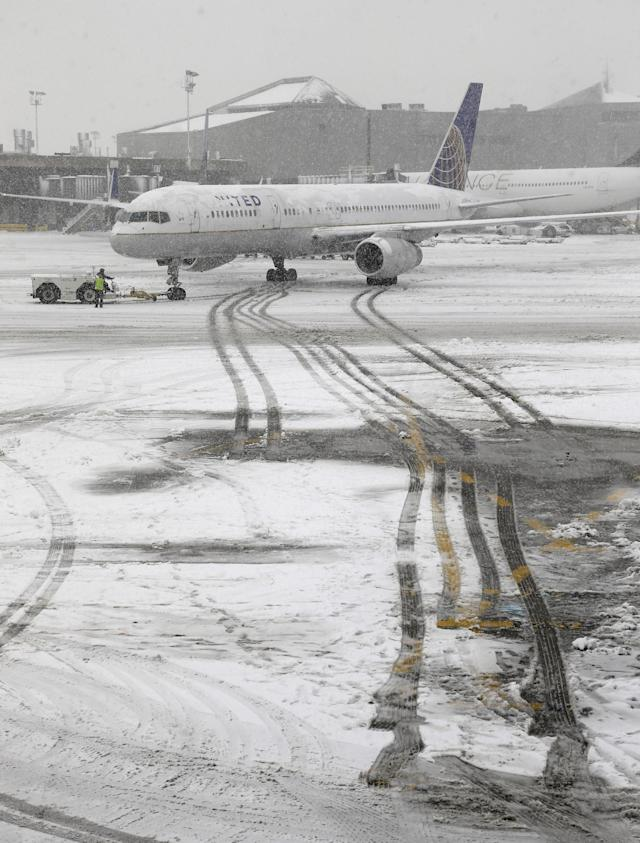A United Airlines airplane leaves tracks in the snow as it is pushed back from a gate Monday, Feb. 3, 2014, at Newark Liberty International Airport in Newark, NJ. A winter storm one day after the Super Bowl cancelled or delayed dozens of flights in the region. (AP Photo/Ted S. Warren)