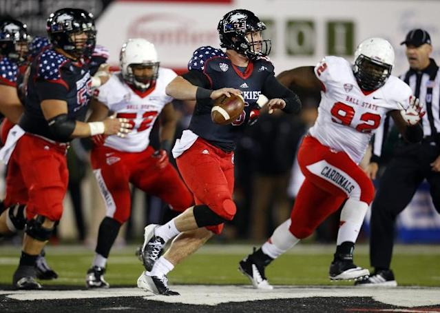 Northern Illinois quarterback Jordan Lynch, center, is chased down by Ball State defensive tackle Nathan Ollie, right, during the first half of an NCAA college football game Wednesday, Nov. 13, 2013, in DeKalb, Ill. (AP Photo/Jeff Haynes)