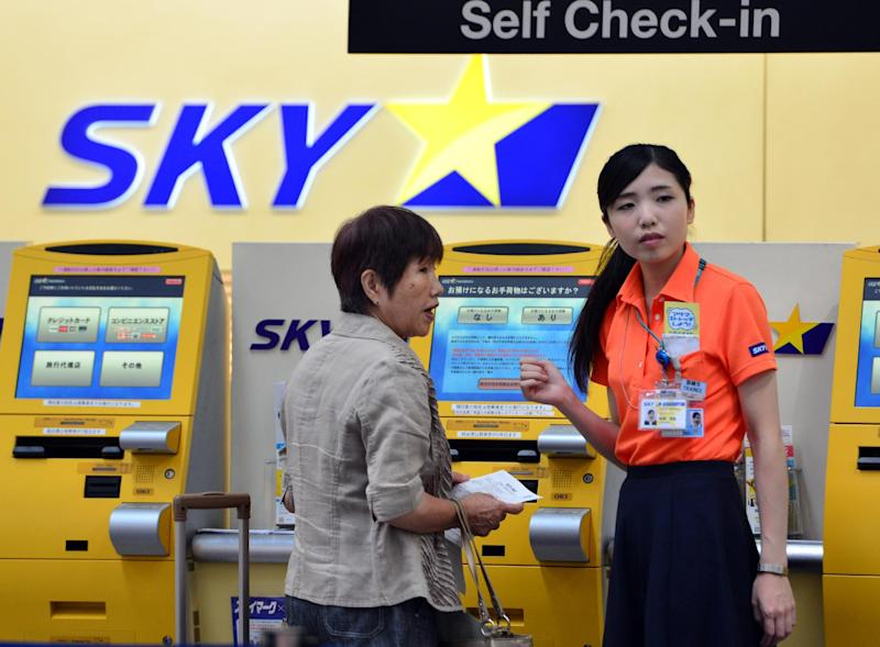 A ground staff member of Skymark Airlines guides a customer at Tokyo's Haneda Airport on July 29, 2014