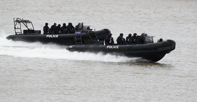 Firearms officers race down the Thames is speedboats (PA)