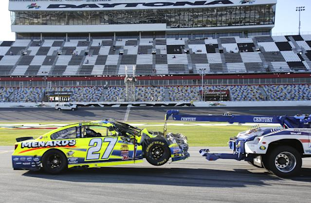 A wrecker tows Paul Menard's wrecked car after a crash during practice for Sunday's NASCAR Daytona 500 auto race at Daytona International Speedway in Daytona Beach, Fla., Wednesday, Feb. 19, 2014. (AP Photo/Terry Renna)