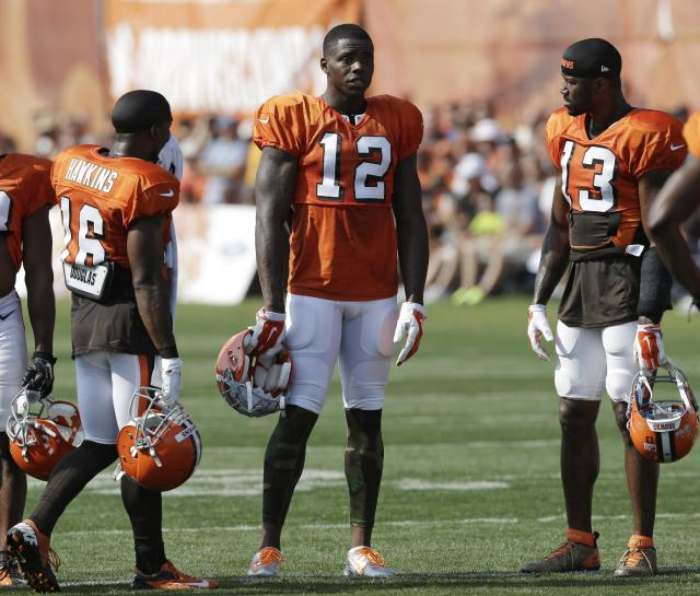 Cleveland Browns wide receiver Josh Gordon (12) talks with teammates Andrew Hawkins (16) and Nate Burleson (13) during practice at the NFL football team's training camp Monday, Aug. 4, 2014, in Berea, Ohio. (AP Photo/Tony Dejak)