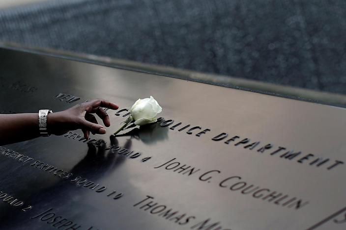 <p>A woman places a single white rose at the edge of the South Pool of the 9/11 Memorial atop the area of the memorial for New York City Police (NYPD) officers killed in the 2001 attacks on the World Trade Center, following the deadly shootings of police officers in Dallas, Texas, in Manhattan, New York, U.S., July 8, 2016. (Photo: Mike Segar/REUTERS) </p>