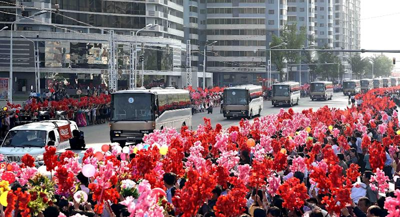 People greet buses carrying developers of the ground-to-ground medium-to-long range strategic ballistic rocket Hwasong-12 in Pyongyang on May 18, 2017 (AFP Photo/STR)