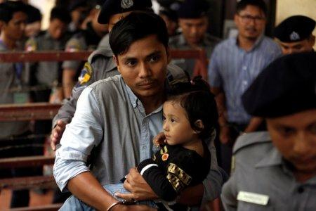 Detained Reuters journalist Kyaw Soe Oo carries his daughter Moe Thin Wai Zin while escorted by police to lunch break during a court hearing in Yangon, Myanmar June 11, 2018. REUTERS/Ann Wang