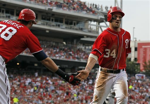 Washington Nationals' Bryce Harper (34) celebrates with Michael Morse after scoring on Adam LaRoche's single during the first inning of a baseball game with the St. Louis Cardinals at Nationals Park Saturday, Sept. 1, 2012, in Washington. (AP Photo/Alex Brandon)