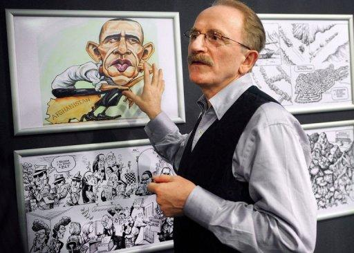 """Kallaugher points to drawing of US President Barack Obama during an exhibition at the National Museum of Contemporary Art in Bucharest. Political cartoons are """"on the frontline of freedom"""" as recent attacks on cartoonists in Iran and Syria showed, famous American cartoonist Kevin KAL Kallaugher told AFP in Bucharest"""
