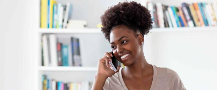 Laughing afro american young adult woman at mobile phone indoors at home